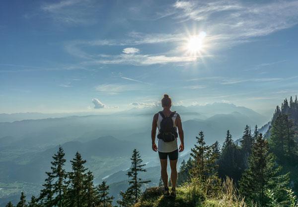 hiker-on-mountain-with-sun